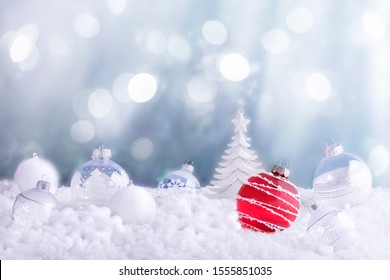 Merry Christmas and Happy New Year Concept. Red Christmas ornament, White Baubles and Christmas Tree On Snow. Abstract background.