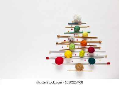 Merry Christmas and Happy New Year: funny Christmas tree made of knitting accessories, woolen balls, knitting needles and crochet hooks on a white background. Copy space, flat lay, mock up, top view