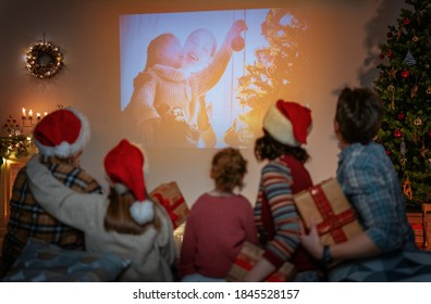 Merry Christmas and Happy New Year! People having fun near tree indoors. Loving family watching holiday movies at home. Granddad, mother, father and daughters spending time together.