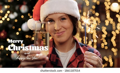 Merry Christmas and happy New Year text. Happy woman smiles and looks at camera, she holding sparkler and glass of champagne in hand, she makes toast gesture. Close-up