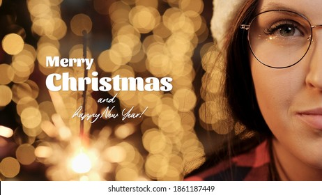 Merry Christmas and Happy New Year text on background of Christmas lights blurry in bokeh, woman face with glasses looking at camera and holding sparkler. Close-up
