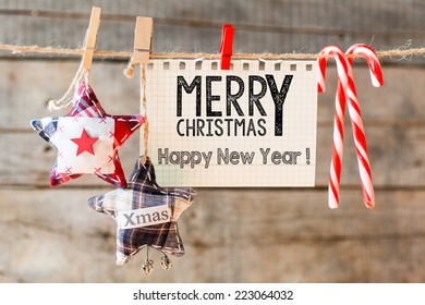 Merry christmas Happy New Year inscription. Merry Christmas Happy New Year inscription on checkered paper attach to rope