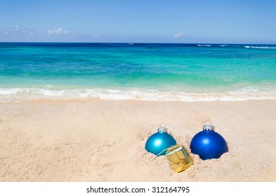 merry christmas and happy new year background with gift and balls on the tropical beach near