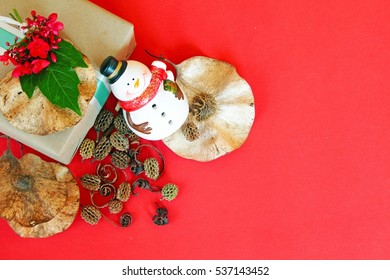 Merry christmas or Happy New Year background concept : Gift box with red flower, snowman, pine cones and dry leaves on red background