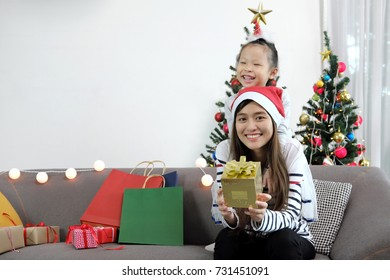 Merry Christmas and Happy New Year holidays. Mom and her cute daughter sitting on sofa near Christmas tree indoors with happiness moment. Portrait family close up.