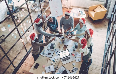 Merry Christmas and Happy New Year 2018! Top view of multiracial young creative people are celebrating holiday in modern office. Group of young business people are drinking champagne in coworking.