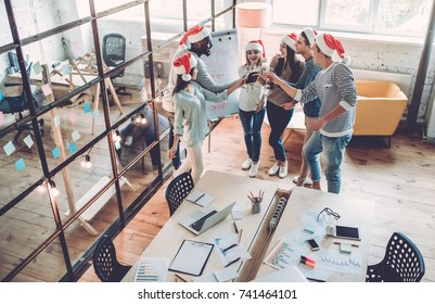 Merry Christmas and Happy New Year 2018!Multiracial young creative people are celebrating holiday in modern office. Group of young business people are drinking champagne and having fun in coworking.