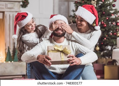 Merry Christmas and Happy New Year! Handsome man is holding a present and smiling while his daughter and wife covering his eyes