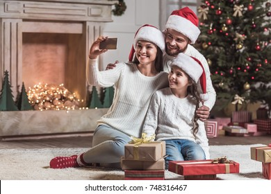 Merry Christmas and Happy New Year! Beautiful mom, dad and daughter in Santa hats are doing selfie using a smart phone and smiling while celebrating