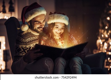 Merry Christmas and Happy New Year! Handsome man is sitting in chair with his little cute daughter in Santa Claus hats and reading book at home. Magic light is coming from the inside.