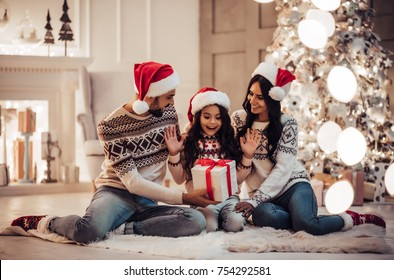 Merry Christmas and Happy New Year! Happy family is waiting for the New Year in Santa Claus hats while sitting near beautiful Christmas tree at home. Parents presenting gift box to charming daughter.