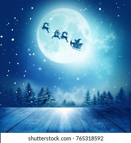Merry christmas and happy new year greeting card with table. Santa and his sleigh flying over snowy landscape