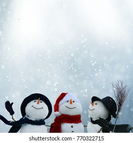 Merry Christmas and happy New Year greeting card with copy-space.Three snowmen standing in winter Christmas landscape.Winter background