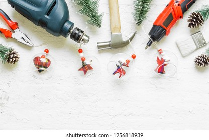 Merry Christmas and Happy New Years Handy Constrcution Tools background concept.  Handy House Fix DIY handy tools with Christmas ornament decoration on a rustic wooden table.