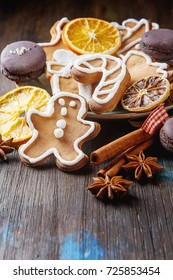 Merry christmas holiday decoration background with ginger man snowflakes snowman and tree cookies. Cinnamon, dry orange, cardamom asterisk. Dark wooden table.