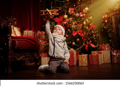 Merry Christmas holidays. Happy little boy plays with airplane at home next to a beautiful Christmas tree. Christmas and New Year concept.