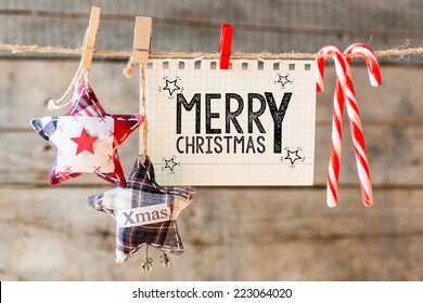 Merry christmas inscription. Merry Christmas inscription on checkered paper attach to rope