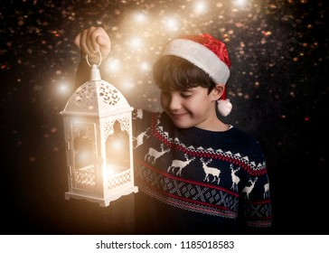 Merry Christmas little boy holding an old flashlight on black background
