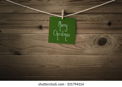 Merry Christmas message written on a square of festive dark green note paper and pegged to a string washing line,  Wood plank fence background.  Retro low saturation and vignette.