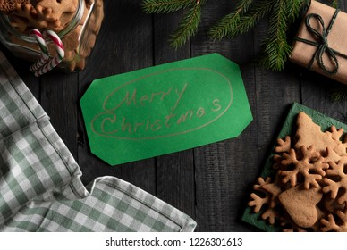 Merry Christmas message wrote on green paper surrounded with gingerbread cookies in a jar and on green napkins, on a black wooden table