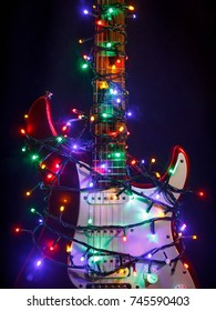 Merry christmas music guitar wrapped by colorful garland as a gift background