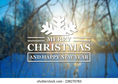 Merry Christmas and New Year greeting card on blurred sun and tree branches at winter sunset on background