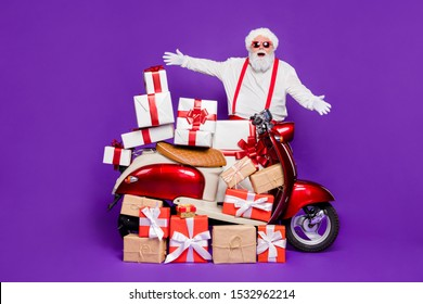 Merry christmas! Photo of fat santa man with many newyear giftboxes on bike congratulating children wear sun specs and red x-mas costume isolated purple background