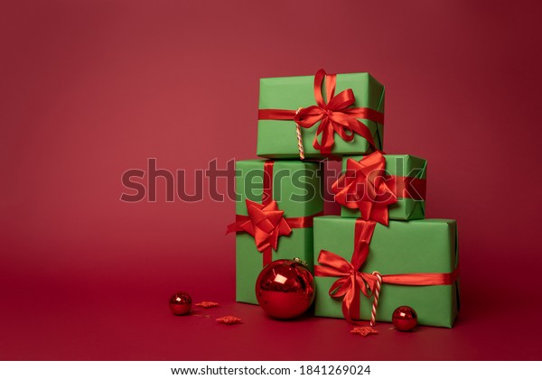 Merry Christmas! Preparing for New year celebration. Christmas composition group of green gift boxes with red ribbons and Christmas balls stand on a red background in the Studio. Layout. Copy space.