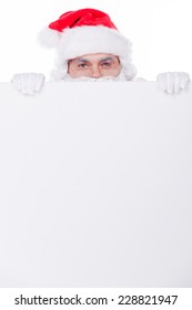 Merry Christmas! Santa Claus looking out of the copy space while being isolated on white