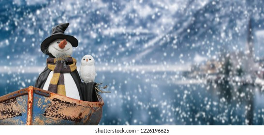 merry christmas snowman on a small boat floating on a lake in a cold winter mountain landscape while snowing