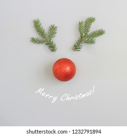 Merry Christmas text and abstract reindeer head  with red nose made of fir branches and red glitter ball. Christmas, holiday, xmas concept. Light blue background.