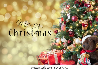 Merry Christmas text card with blurred sparkle background and bright decorated Xmas tree.