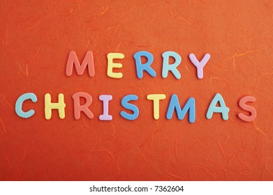 Merry christmas text (colorful soft rubber letters) on red silk paper