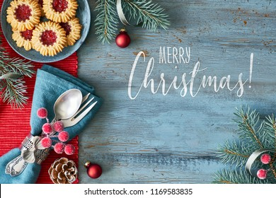 """Merry Christmas"" text on rustic board framed with various Xmas decorations in red and blue, including decorated crockery"