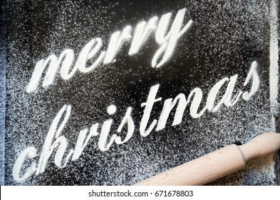 merry Christmas text printed with flour on a metal sheet