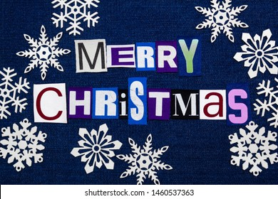 Merry Christmas text word collage surrounded by white paper snowflakes, multi colored fabric on blue denim, winter holiday, horizontal aspect