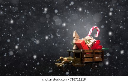 Merry Christmas. Toy car full of Xmas gifts. Presents on noel evening. Xmas tree, traditional candy with christmas ornaments, heart. Christmas night. Snowing.