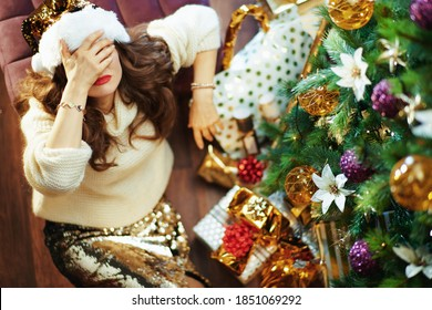 Merry Christmas. Upper view of stressed modern female in gold sequin skirt and sweater near Christmas tree and gift boxes.