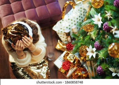 Merry Christmas. Upper view of stressed elegant middle aged housewife in gold sequin skirt and sweater near Christmas tree and gift boxes.