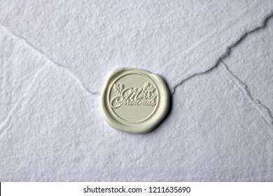 Merry Christmas wax seal stamp on white rag cotton envelope. Script font holly round seasonal.  Sealing wax.