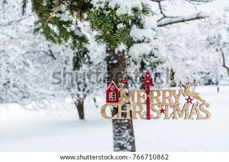 merry christmas wooden sign hanging on a snowy pine tree christmas card - Merry Christmas Wooden Sign