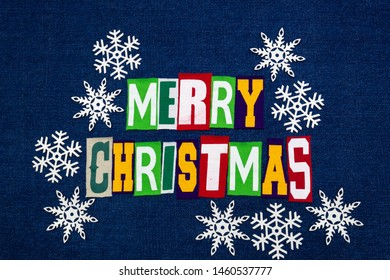 Merry Christmas word text collage typography, multi colored fabric on blue denim, paper snowflakes winter holiday, horizontal aspect