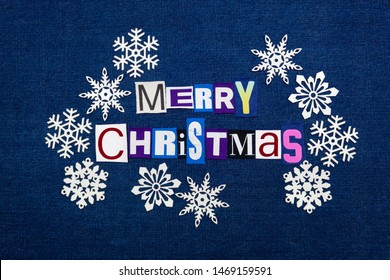 Merry Christmas word text collage surrounded by white paper snowflakes, multi colored fabric on blue denim, winter holiday, horizontal aspect