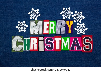 Merry Christmas word text collage with white paper snowflakes, multi colored fabric on blue denim, winter holiday, horizontal aspect