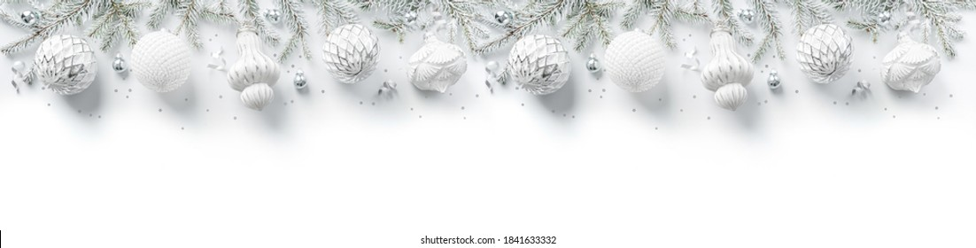 Merry Christmas wreath made of fir branches, white and silver decorations, sparkles and confetti on white background. Xmas and New Year holiday, bokeh, light. Flat lay, top view, wide banner