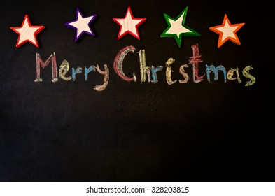 Merry Christmas written with chalk on a black background with wooden toys. the toning. selective focus