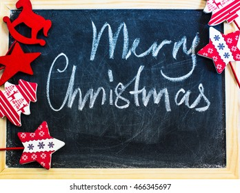 Merry Christmas written with chalk on a chalkboard with traditional christmas decorations