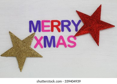 Merry Christmas written with colorful letters and red and golden stars
