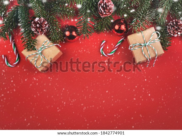 Merry Christmas.Christmas concept background.Christmas tree branches and Christmas gifts with snowflakes over red background