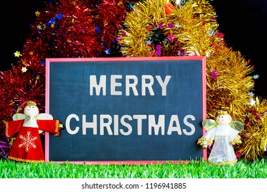 Merry Christmas,Holiday decoration and snow man on green grass with chalkboard